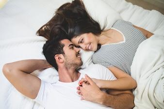 Pareja tumbada en la cama agarrada de la mano y mirándose a los ojos