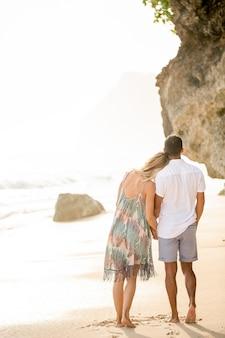 Pares cariñosos que dan un paseo en la playa