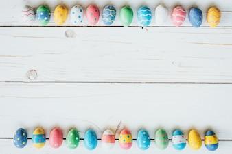 Pascua de huevos de colores sobre fondo de madera blanca con espacio para texto.
