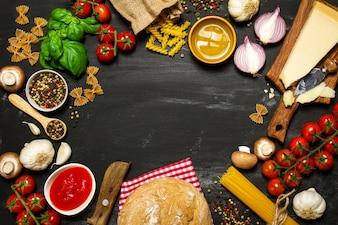 Pasta cruda con tomates y queso sobre una mesa negra haciendo un círculo