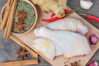 Patas de pollo crudo en la tabla de cortar