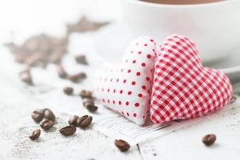 Peluche con forma de corazón a cuadros blancos y rojos y otro con bolitas rojas