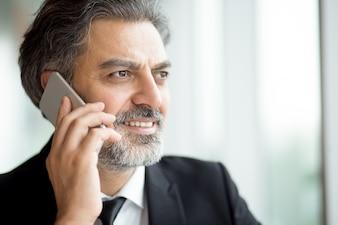 Pensativo hombre de negocios senior con barba usando el teléfono
