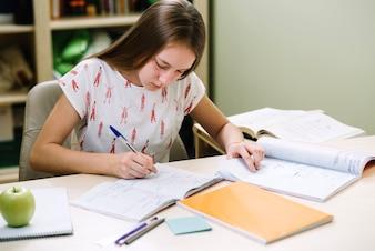 Pensativo niña sentada y escribiendo