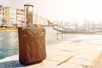 Pequeña maleta sobre fondo urbano de viajes, Venecia, Italia. Horizontal. Viraje. Concepto De Las Vacaciones Del Viaje.