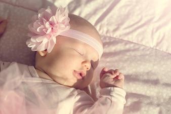 Pequeña niña linda miente y duerme en su cama, sosteniéndola mano en la boca. Hermosa luz del sol. Horizontal.