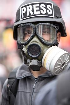 Periodista con una máscara de gas