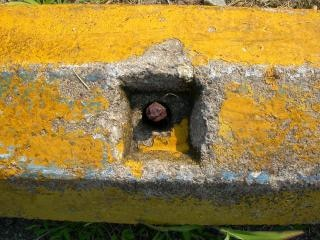 perno oxidado en el muro de hormigón amarillo