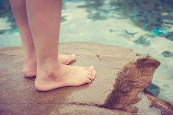 Persona de pie encima de una roca mirando al mar