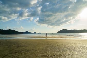 Persona en mitad de una playa desierta