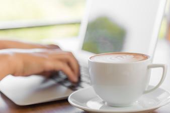 Persona trabajando en un portátil con una taza de café al lado