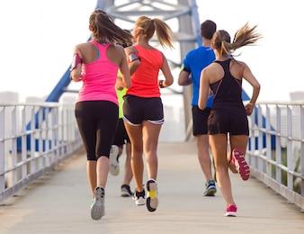 Personas corriendo por un puente