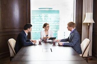 Personas de negocios sentadas en una gran mesa de madera con un portátil