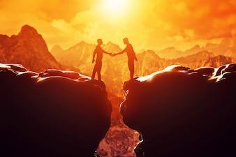 Personas en un acantilado dándose un apretón de manos