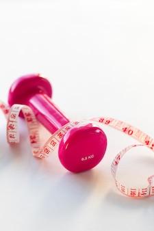 Pesas rosas y una cinta métrica