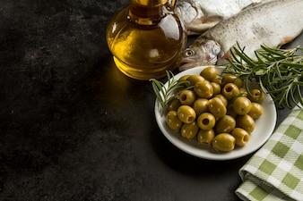 Pescado, aceite de oliva y aceitunas sobre superficie negra