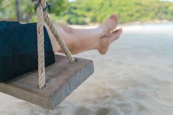 Pierna de la mujer en un columpio en el mar tropical playa