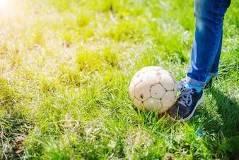 Piernas con un balón al aire libre
