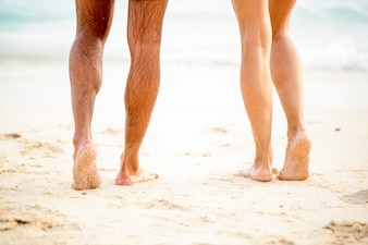 Piernas de joven pareja de pie en la arena de la playa