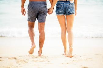 Piernas de la joven pareja caminando en la arena a la playa
