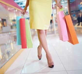 Piernas en primer plano de mujer caminando por el centro comercial