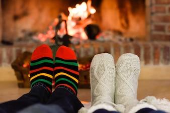 Pies con calcetines de navidad cerca de una chimenea