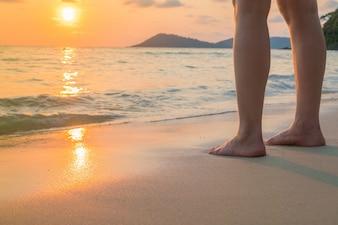 Pies en la arena en la puesta del sol