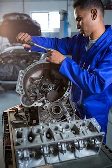 Pieza del motor de reparación del mecánico con la carraca