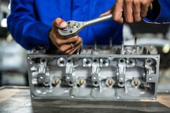 Pieza del motor de reparación Mecánico con el trinquete en el garaje de reparación