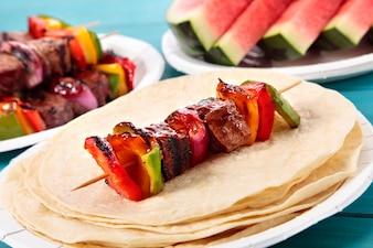 Pincho de barbacoa con carne y verduras en la mesa de picnic