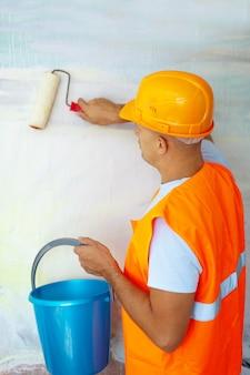 Pintores de casas con rodillo de pintura en la casa