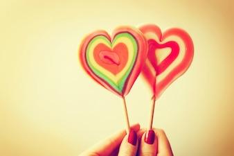 Piruleta con forma de corazón sujetada por una mano