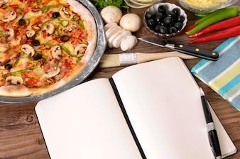Pizza con el cuaderno o libro de cocina y los ingredientes