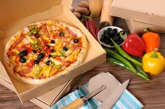 Pizza en una caja de entrega con los ingredientes