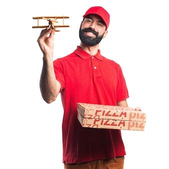 Pizza entrega hombre sosteniendo un avión de juguete de madera