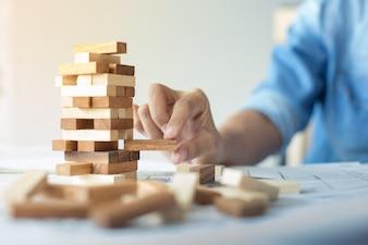 Planificación, riesgo y estrategia en los negocios, empresario y ingeniero de juegos de azar colocación de bloques de madera en una torre.