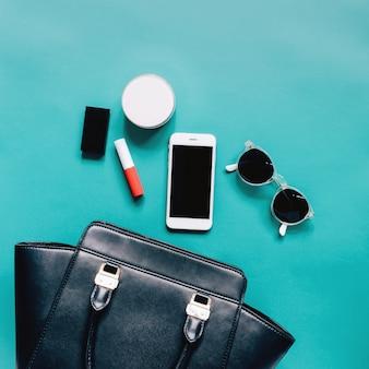Plano de la mujer de cuero negro bolsa abierta con cosméticos, accesorios y teléfonos inteligentes sobre fondo verde
