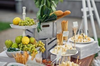 Plato cansado con limones y soportes de uva en la mesa con queso