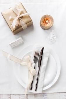 Plato con cubiertos bien decorados con una vela encendida