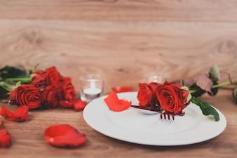 Plato con cubiertos y rosas y velas encendidas de fondo