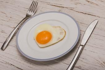 Plato con cubiertos y un huevo frito