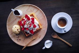 Plato con una tostada con nata y fresas y un café