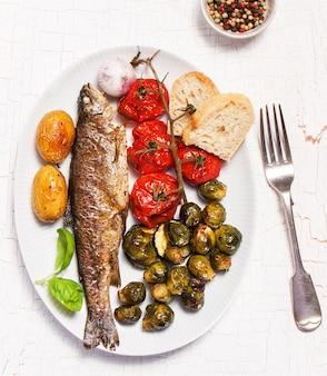 Plato de pescado cocinado con verduras y pan