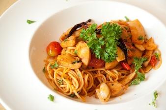 Plato recién cocinado de espaguetis con salchicha salpicado de hierbas verdes frescas.
