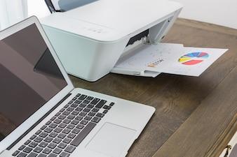 Portátil en una mesa de madera con una impresora