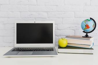Portátil, globo terráqueo, manzana y libros