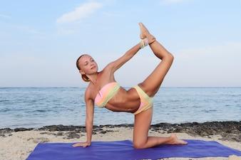 Práctica del yoga. Mujer delgada practicando por el mar