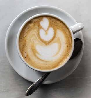 Precioso sabroso café cappuccino en blanco taza con cuchara en la pestaña