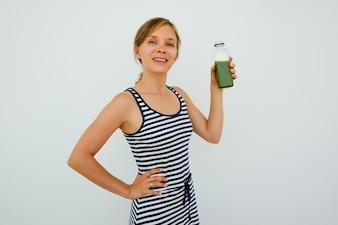Pretty Woman Holding botella de jugo verde fresco