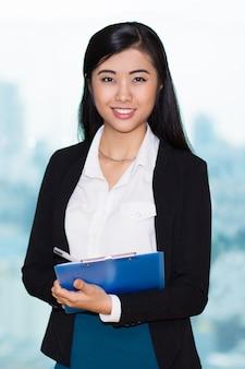 Primer de la mujer asiática fascinante con el sujetapapeles